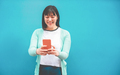 Asian woman using smartphone with blue background - PhotoDune Item for Sale