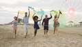 Young friends running with smoke bombs and champagne bottle at beach festival - PhotoDune Item for Sale