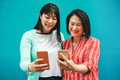 Asian mother and daughter using smartphone with blue background - PhotoDune Item for Sale