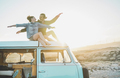 Happy couple sitting on top of minivan roof at sunset - PhotoDune Item for Sale