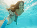 Happy couple taking selfie under the water in swimming pool resort with special photo video camera - PhotoDune Item for Sale