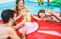 Happy friends drinking cocktails and eating tropical fruit at swimming pool party - PhotoDune Item for Sale