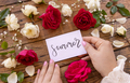 Woman hands holding SUMMER card near flowers on a wooden table - PhotoDune Item for Sale