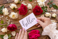 Woman hands holding HELLO card near flowers on a wooden table - PhotoDune Item for Sale