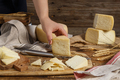 Hand put piece of  fresh homemade cheese on a wooden board - PhotoDune Item for Sale