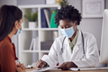 Female Doctor In White Coat Wearing Face Mask Having Meeting With Mature Woman Patient In Office - PhotoDune Item for Sale