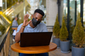 African businessman wearing face mask and social distancing while sitting at coffee shop using - PhotoDune Item for Sale