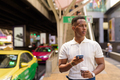 Portrait of young African businessman wearing casual clothes while using mobile phone and holding - PhotoDune Item for Sale