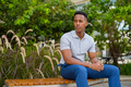 Portrait of young African businessman wearing casual clothes and sitting at park bench while - PhotoDune Item for Sale