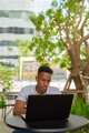 Portrait of young African businessman wearing casual clothes and sitting at coffee shop using laptop - PhotoDune Item for Sale