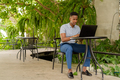 Portrait of young African businessman wearing casual clothes and sitting at coffee shop while using - PhotoDune Item for Sale
