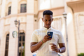 Portrait of young African businessman wearing casual clothes while texting with mobile phone and - PhotoDune Item for Sale