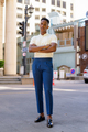 Full length shot of young African businessman outdoors in city streets looking at camera with arms - PhotoDune Item for Sale