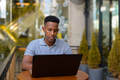 African businessman sitting at coffee shop while using laptop computer - PhotoDune Item for Sale