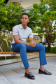 Full length shot of young African businessman wearing casual clothes and sitting at park bench while - PhotoDune Item for Sale