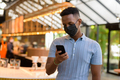 African businessman wearing face mask in coffee shop restaurant while social distancing and using - PhotoDune Item for Sale
