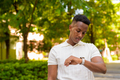 Portrait of young African businessman wearing casual clothes and looking time from wristwatch at - PhotoDune Item for Sale