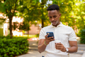 Portrait of young African businessman wearing casual clothes and using mobile phone and holding - PhotoDune Item for Sale