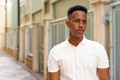 Portrait of young African businessman wearing casual clothes at city street while thinking - PhotoDune Item for Sale