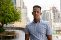 Portrait of young African businessman wearing casual clothes at rooftop garden - PhotoDune Item for Sale