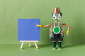 Advertising project on a wooden easel. Robot with blank blue paper poster - PhotoDune Item for Sale