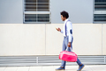 Black man with afro hairstyle carrying a sports bag and smartphone outdoors - PhotoDune Item for Sale