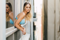 Young woman in lingerie leaning out the window of her room - PhotoDune Item for Sale