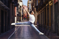 Young black man doing an acrobatic jump in the middle of the street - PhotoDune Item for Sale