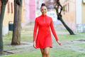 Smiling mixed woman in red dress walking down the street - PhotoDune Item for Sale