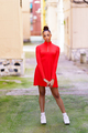 Young black woman in red dress posing on a street with colorful walls - PhotoDune Item for Sale