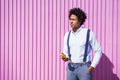 Black man with afro hairstyle carrying a sports bag and smartphone in yellow background - PhotoDune Item for Sale