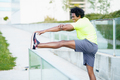 Black man with afro hair doing stretching after running outdoors - PhotoDune Item for Sale