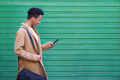 Black young man using a smartphone near a urban wall - PhotoDune Item for Sale