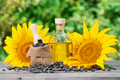 Bottle of sunflower oil and sunflower with seeds on wooden table - PhotoDune Item for Sale