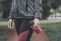 Female jogger holding bottle of refreshing strawberry juice in park - PhotoDune Item for Sale