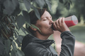 Female jogger drinking refreshing strawberry juice in park - PhotoDune Item for Sale