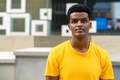 Portrait of handsome black African man wearing yellow t-shirt outdoors in city during summer - PhotoDune Item for Sale