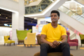 Portrait of handsome black African man wearing yellow t-shirt while sitting and thinking - PhotoDune Item for Sale