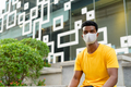 African man wearing yellow t-shirt and face mask outdoors in city - PhotoDune Item for Sale