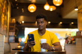 African man wearing yellow t-shirt in coffee shop while using mobile phone - PhotoDune Item for Sale