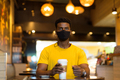 Portrait of handsome black African man wearing yellow t-shirt in coffee shop - PhotoDune Item for Sale