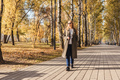 Woman walking in autumn park with coffee. - PhotoDune Item for Sale
