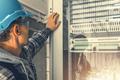 Telecommunication Technician Looking Inside Servers Rack - PhotoDune Item for Sale
