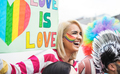 Young woman holding lgbt banner at a gay pride parade - Focus on female face - PhotoDune Item for Sale