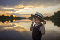 Girl in summer straw hat pulling hand forward to sunset on lake, lifestyle, local travel - PhotoDune Item for Sale