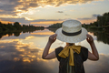 Girl in summer straw hat looking at sunset on lake, lifestyle, local travel, back view - PhotoDune Item for Sale