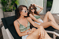 Two attractive stylish women in summer outfit lying on chaise lounge on modern terrace in sunshine. - PhotoDune Item for Sale