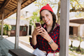 Attractive cute girl with dark hair dressed in red cap and plaid shirt scrolling on smartphone - PhotoDune Item for Sale