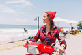 Hipster lady dressed in plaid shirt and red cap drives on the red bike in sunlight - PhotoDune Item for Sale