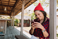 Hipster cute woman dressed red cap stands outside on wood terrace with smartphone - PhotoDune Item for Sale